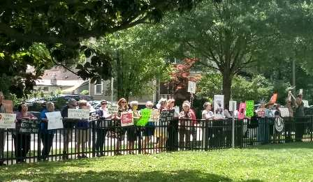 Participants along fence outside of Senator Tillis' office in Raleigh