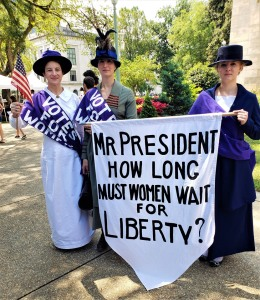 3 women in suffrage costumes